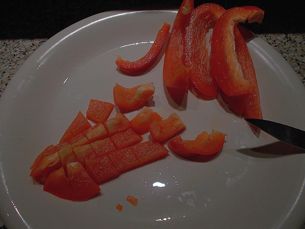 Schneiden Sie die Paprika in Streifen und anschließend in Würfel.